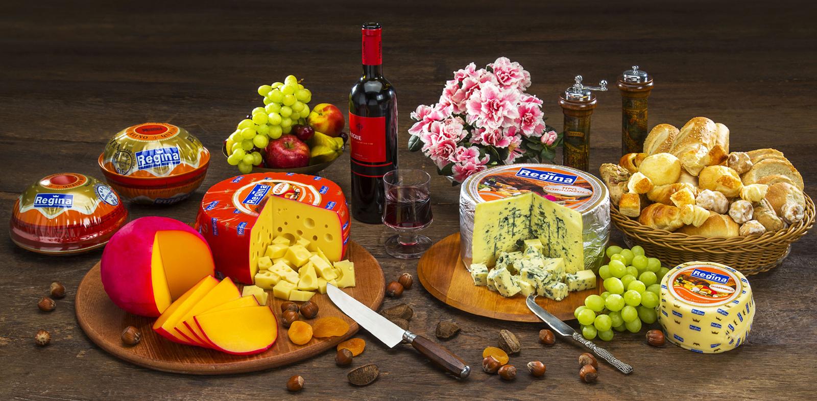 Mesa de queijos, com decoração em flores, vinho e taça.